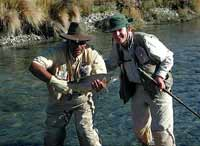 Another happy fly fisherman lands a trout in New Zealand.